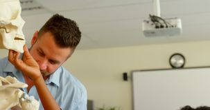 Kaukasische mannelijke leraar die menselijk skeletmodel in klaslokaal bevestigen op school 4k stock video