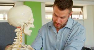 Kaukasische mannelijke leraar met menselijk skeletmodel in klaslokaal op school 4k stock videobeelden