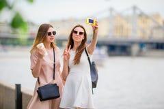 Kaukasische meisjes die selfie tot achtergrond maken grote brug Jonge toeristenvrienden die bij vakantie in openlucht gelukkig gl royalty-vrije stock foto's