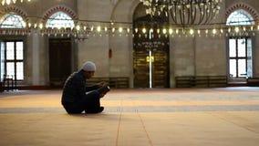 Kaukasische mens aan het lezen van Quran bij de moskee stock footage