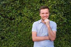 Kaukasische mens in blauw overhemd die zich dichtbij groene grasmuur bevinden Hij glimlacht en voelt zeker Royalty-vrije Stock Afbeeldingen