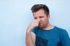 Kaukasische mens in blauw overhemd die zijn neus wegens stank sluiten Stock Afbeeldingen