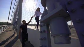 Kaukasische mens die het meisje leiden door de hand van de brug in langzame motie stock footage