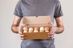 Kaukasische mens die met grijze t-shirt een de dooshoogtepunt van het kartonei van kippeneieren houden op een witte achtergrond royalty-vrije stock foto