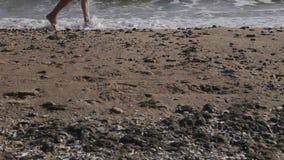 Kaukasische mens die naakte voet op zandig strand in werking stellen in overzeese golf stock video