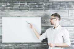 Kaukasische mens die op whiteboard richten Stock Foto's