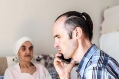 Kaukasische mens met stoppelige baard die en slecht nieuws op de telefoon spreken ontvangen stock foto