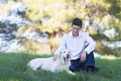 Kaukasische mensen die van vrije tijd met zijn hond van Labrador genieten Stock Foto's
