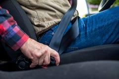 Kaukasische mensen vastmakende veiligheidsgordel in auto royalty-vrije stock foto's