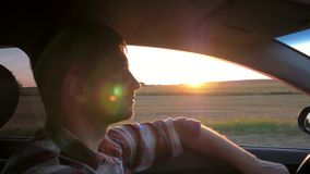 Kaukasische Mensenaandrijving in de Auto op de Achtergrond van de Zonsondergang stock videobeelden
