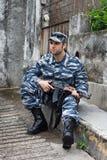 Kaukasische militaire mens in van de stedelijke oorlogvoeringszitting en holding auto Stock Afbeeldingen