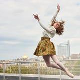 Kaukasische Modeballerina, die auf das Dach springt Stockfoto