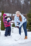 Kaukasische Mutter und Tochter, die den Schneemann, Kamera betrachtend macht Stockfotos