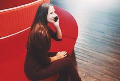 Kaukasische onderneemster die terwijl het zitten op rode bank telefoneren stock fotografie