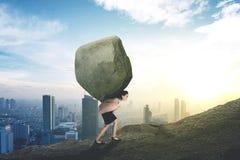 Kaukasische onderneemster opheffende steen op de heuvel stock foto's