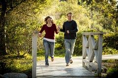 Kaukasische Paare, die auf Brückenholdinghände laufen Stockfotos