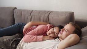 Kaukasische Paare, die auf dem Sofa zusammen zu Hause umfassend liegen Reizende Freundin, die seinen Freund streichelt An sich en stock video