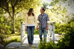 Kaukasische Paare, die auf im Freien hölzerne Brücke gehen Lizenzfreies Stockbild