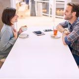 Kaukasische Paare, die an einander auf Datum im Café lächeln Stockbild
