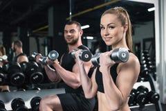 Kaukasische Paare von den Athleten, die zusammen mit Dummköpfen an der Turnhalle ausbilden lizenzfreie stockfotografie