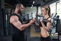 Kaukasische Paare von den Athleten, die zusammen mit Dummköpfen an der Turnhalle ausbilden lizenzfreies stockfoto