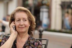 Kaukasische reife Frau, die telefonisch draußen nennt Stockfoto