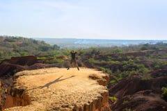 Kaukasische Kaukasische reiziger die in sportkleding van het geluk van vrijheid op een rots op de achtergrond van aard springen stock foto
