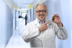 Kaukasische rijpe mannelijke arts op heldere achtergrond Stock Foto