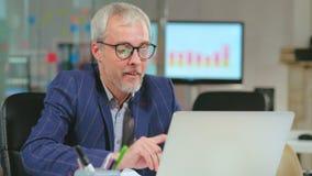Kaukasische rijpe zakenman die aan computer werken stock videobeelden