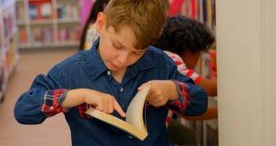 Kaukasische schooljongen die een boek in de bibliotheek 4k lezen stock footage