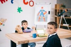 Kaukasische schooljongens die lunch eten terwijl het zitten bij houten lijst Stock Afbeelding