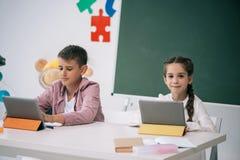 Kaukasische Schulkinder unter Verwendung der digitalen Tabletten beim in der Klasse zusammen studieren Stockbilder