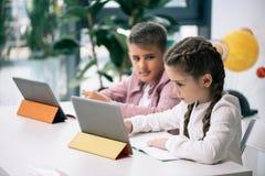 Kaukasische Schulkinder unter Verwendung der digitalen Tabletten beim in der Klasse zusammen studieren Lizenzfreies Stockbild