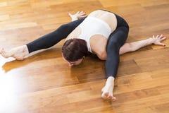 Kaukasische Sportieve Vrouw die Yoga doen die binnen praktizeren Het zitten in Rug en Benen Gescheiden Gespleten Uitrekkende Houd royalty-vrije stock foto