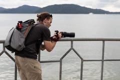 Kaukasische Tattoed-Mensenfotograaf Taking Pictures Traveler dichtbij royalty-vrije stock fotografie
