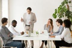 Kaukasische teamleider die Afrikaanse werknemer voor fout berispen bij m stock afbeeldingen