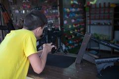 Kaukasische Teenagertrieb an den Zielen mit pneumatischem Gewehr in einem Saal, hintere Ansicht stockbilder