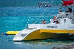Kaukasische toeristen die van dranken op zonnige dag aan boord van een catamaran in Montego Bay Jamaïca genieten stock foto's