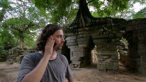 kaukasische touristische Unterhaltung mit Handy, Ruinen im tropischen Dschungel stock video footage