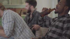 Kaukasische twee en Afrikaanse Amerikaanse mensen één die op de bank zitten Drie mensen die samen thuis het drinken bier zitten stock footage