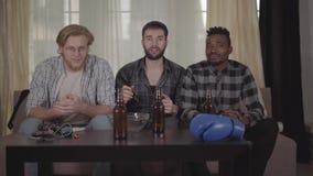Kaukasische twee en Afrikaanse Amerikaanse mensen één die samen, het letten op het in dozen doen op TV thuis rusten Bierflessen stock videobeelden
