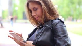 Kaukasische volwassen vrouw vrouwelijke het gebruiken smartphone van iphonecellphone op straat stock videobeelden
