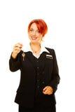 Kaukasische vrouw als hotelarbeider die sleutel aanbiedt Stock Afbeelding
