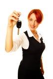 Kaukasische vrouw als hotelarbeider die sleutel aanbiedt Stock Fotografie