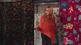 Kaukasische vrouw die door rijen van batikstof lopen stock video
