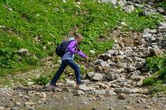 Kaukasische vrouw die een bergkreek kruisen bij een wandelingsreis Stock Afbeelding