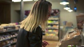 Kaukasische vrouw die kruidenierswinkelsgoed bekijken bij supermarkt die te kopen wat beslissen Het zetten van producten intobask stock videobeelden