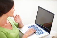 Kaukasische vrouw die laptop binnen met behulp van stock fotografie