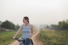 Kaukasische vrouw die zich met fiets in plattelandsweg bevinden stock foto