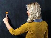 Kaukasische vrouw die zich voor een donker bord bevinden Het schilderen Stock Foto